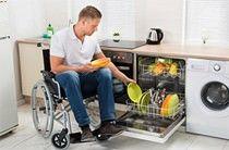Rollstuhlfahrer räumt die Spülmaschine in seiner barrierefreien Küche ein