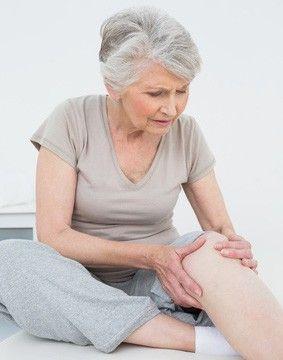 Une femme a mal au genou lors de la montée des escaliers