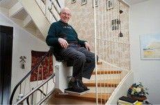 Mann nimmt Probefahrt mit Treppenlift vor