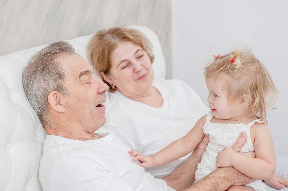 Versicherung für Rentner: Opa und Oma mit Enkelkind