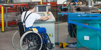 Rollstuhlfahrer arbeitet in Werkstatt