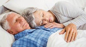 Seniorenpaar liegt glücklich im Bett