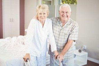 Seniorenpaar steht glücklich im geräumigen Schlafzimmer