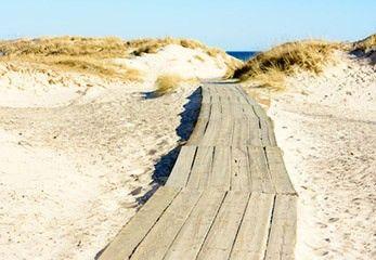Ein Holzsteg ermöglicht einen barrierefreien Strandzugang für Rollstuhlfahrer und Menschen mit Gehhilfe